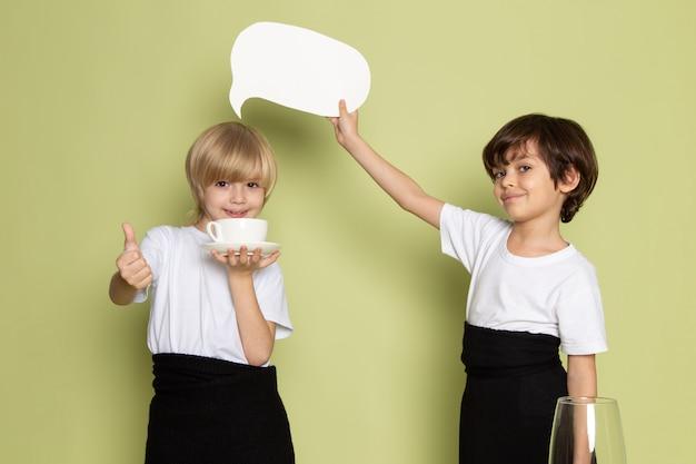 Una vista frontal dos niños sonrientes adorables con camisetas blancas en el escritorio de color piedra