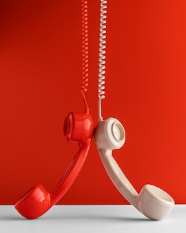 Vista frontal de dos receptores telefónicos colgando del cable