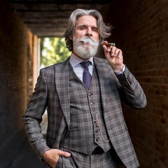 Vista frontal elegante hombre maduro fumando