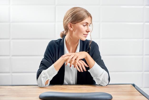 Vista frontal de la elegante mujer mirando a un lado y mostrando la nueva manicura.