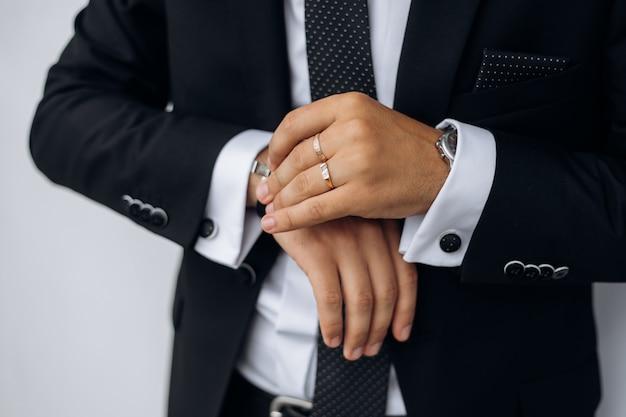 Vista frontal del elegante traje negro del hombre y la mano del hombre sostiene reloj