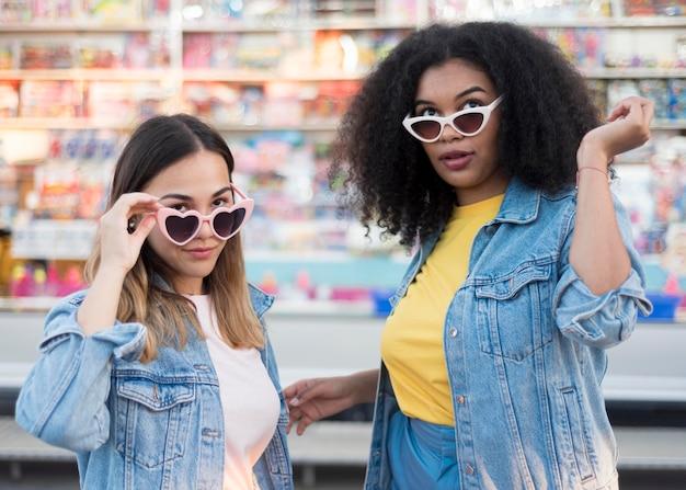 Vista frontal elegantes chicas jóvenes con gafas de sol