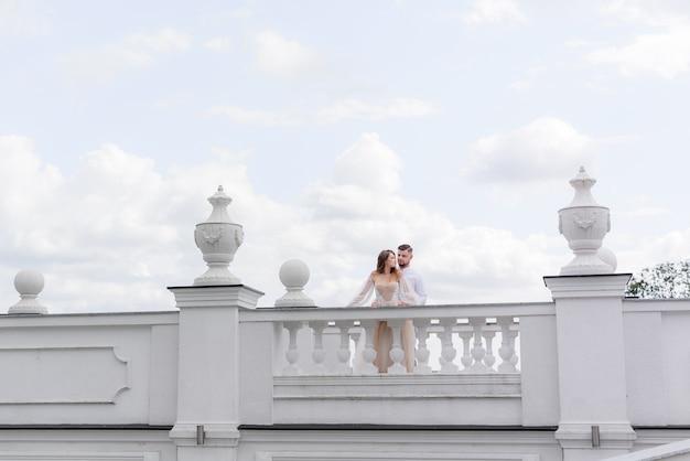 Vista frontal de elegantes novios de pie sobre un puente blanco sobre un fondo de cielo azul