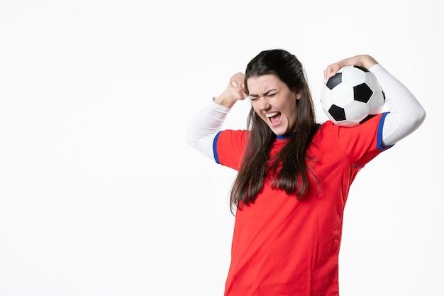 Vista frontal emocional mujer joven en ropa deportiva con balón de fútbol
