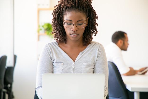 Vista frontal de la empleada enfocada escribiendo en la computadora portátil