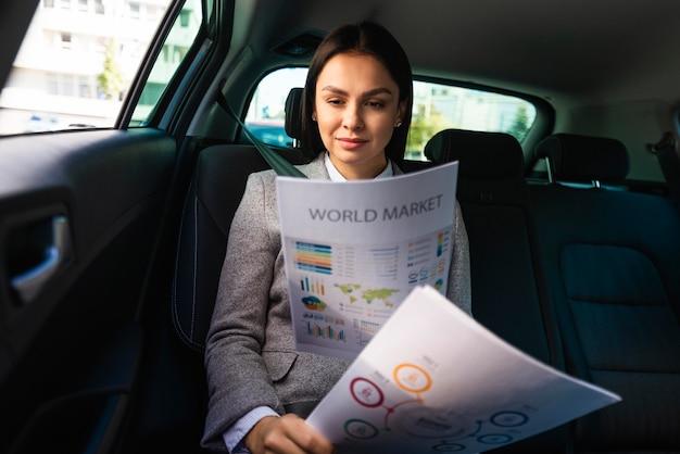 Vista frontal de la empresaria en el coche revisando documentos