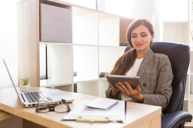 Vista frontal de la empresaria en el escritorio trabajando en tableta