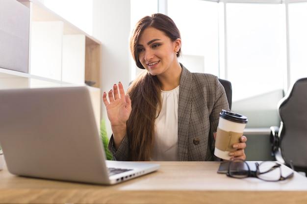 Vista frontal de la empresaria en el escritorio con una videollamada