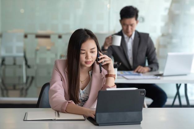 Vista frontal de la empresaria hablando por teléfono y usando la tableta portátil colocada en la mesa de la oficina, la parte posterior está borrosa.