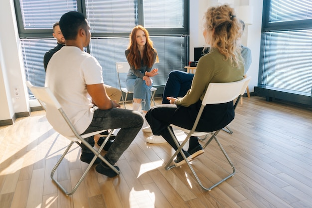 Vista frontal de la empresaria joven pelirroja confiada hablando y discutiendo nuevas ideas con el equipo de negocios creativo, durante la lluvia de ideas de proyectos de puesta en marcha en la sala de la oficina moderna junto a la ventana.
