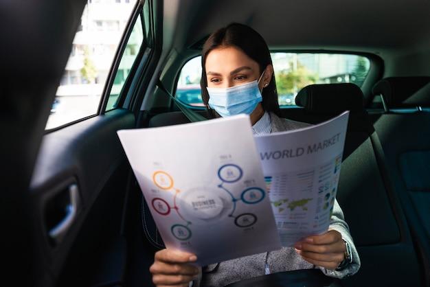 Vista frontal de la empresaria con máscara médica en el coche revisando documentos