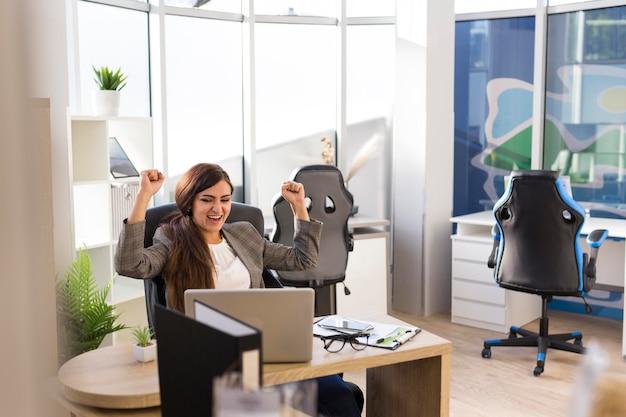 Vista frontal de la empresaria saliendo victoriosa en la oficina