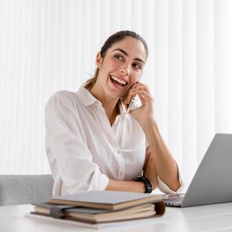 Vista frontal de la empresaria sonriente trabajando con smartphone y portátil