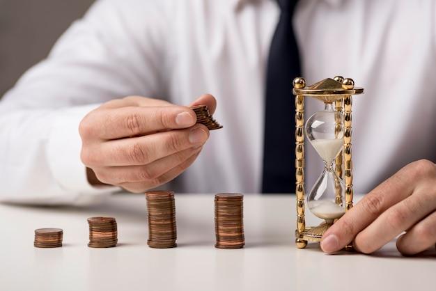 Vista frontal del empresario con monedas y reloj de arena