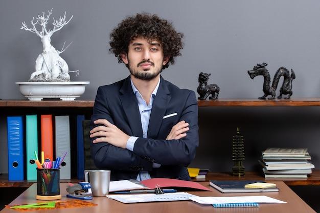 Vista frontal empresario seguro cruzando las manos sentados en el escritorio en la oficina