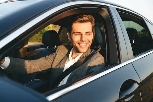 Vista frontal del empresario sonriente en traje de conducción