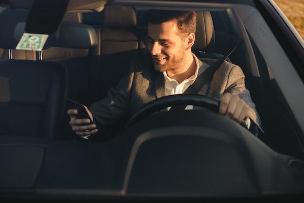 Vista frontal del empresario sonriente en traje de conducir su automóvil