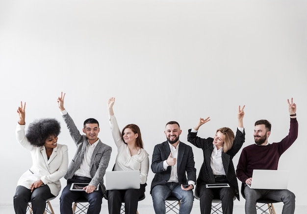 Vista frontal de empresarios con las manos arriba