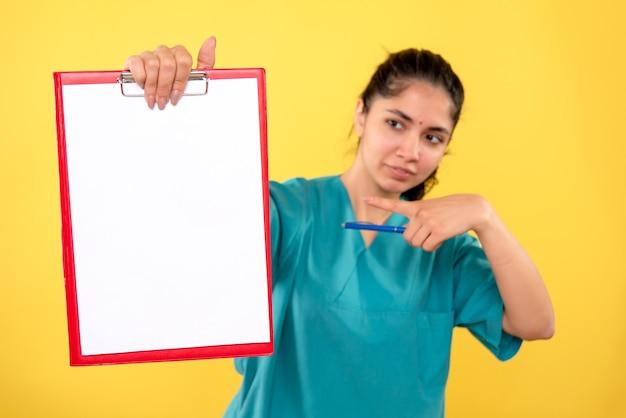 Vista frontal encantadora doctora apuntando al portapapeles sobre fondo amarillo