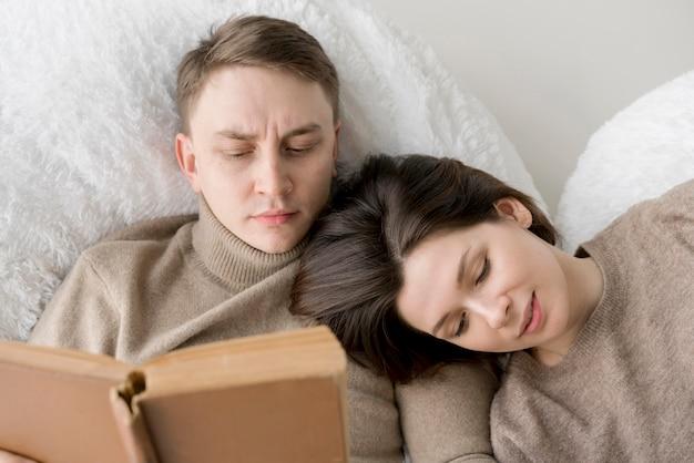 Vista frontal de la encantadora pareja leyendo
