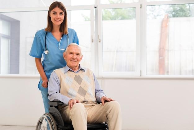 Vista frontal enfermera y anciano mirando a la cámara