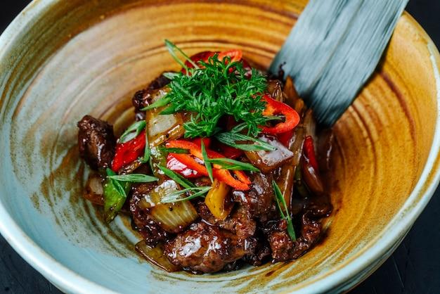 Vista frontal ensalada de carne con verduras y hierbas con salsa en un plato