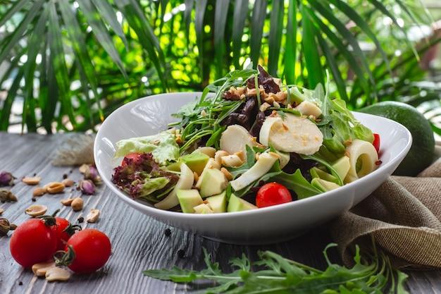 Vista frontal ensalada fresca con rúcula aguacate y tomate