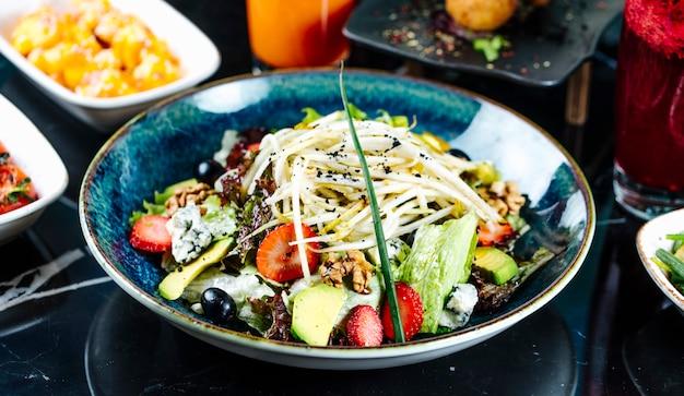 Vista frontal ensalada de verduras con frutas, fresas y uvas en un plato