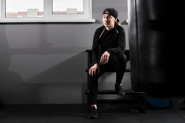 Vista frontal del entrenador boxer posando en el gimnasio