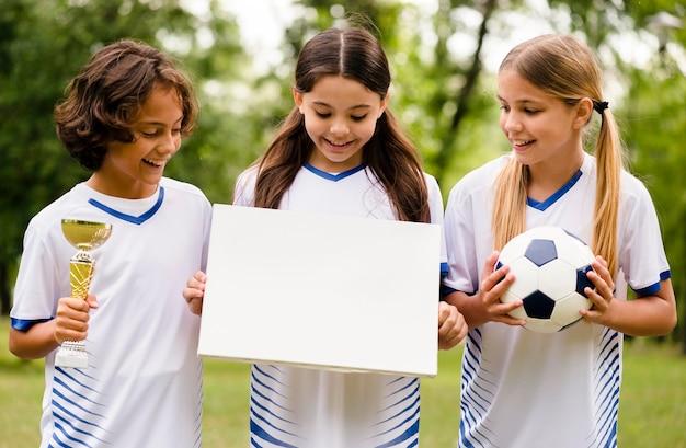 Vista frontal del equipo de fútbol ganador con una tarjeta vacía