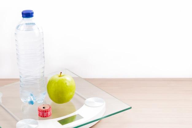 Vista frontal de la escala en la mesa de madera con botella de agua, cinta métrica, manzana y fondo blanco.