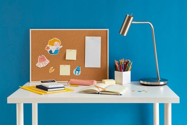 Vista frontal del escritorio para niños con lámpara y portátil.