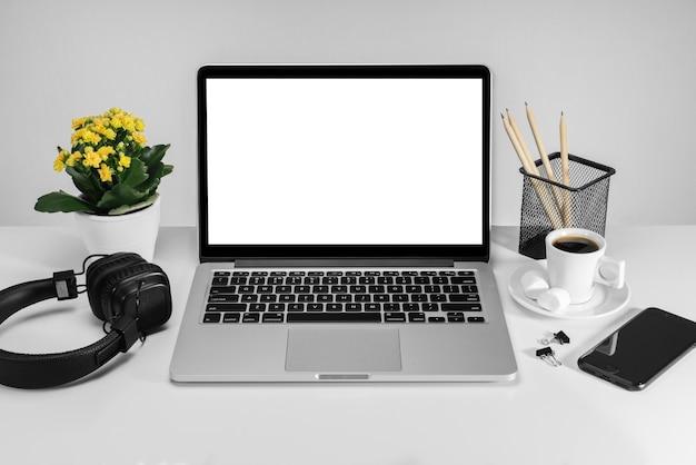 Vista frontal del escritorio de oficina con computadora portátil con pantalla en blanco
