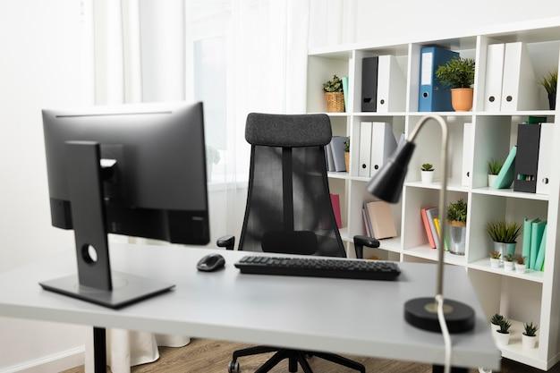 Vista frontal del escritorio de oficina con computadora y silla