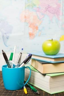 Vista frontal del escritorio con útiles escolares y una manzana.