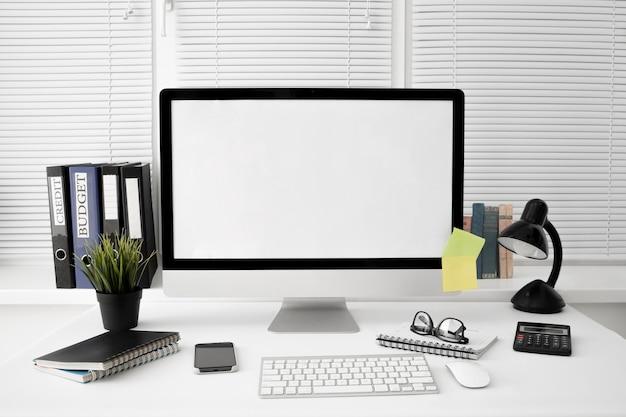 Vista frontal del espacio de trabajo con lámpara y pantalla de computadora