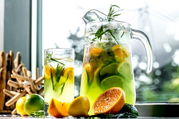Vista frontal estimulante limonada con limón, lima, naranja y estragón