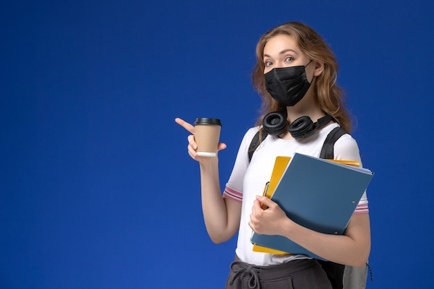 Vista frontal de la estudiante en camisa blanca con mochila máscara negra sosteniendo café y archivos en el escritorio azul