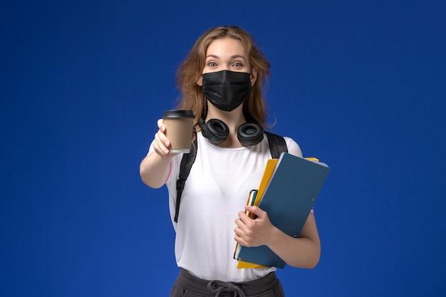 Vista frontal de la estudiante en camisa blanca con mochila máscara negra sosteniendo café y archivos en la pared azul