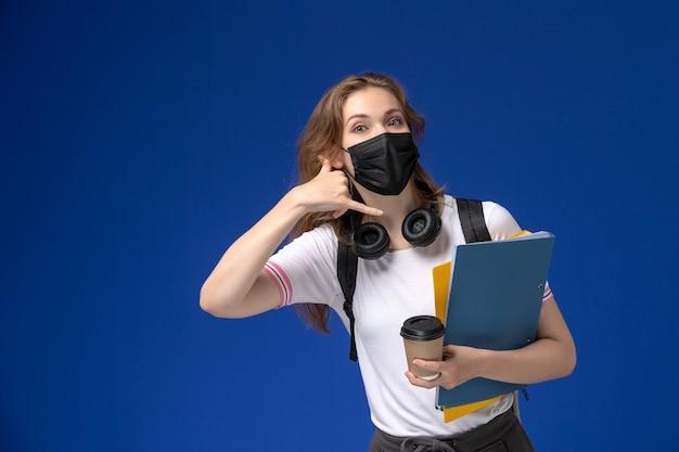 Vista frontal de la estudiante en camisa blanca con mochila negro máscara estéril sosteniendo café y archivos posando en la pared azul