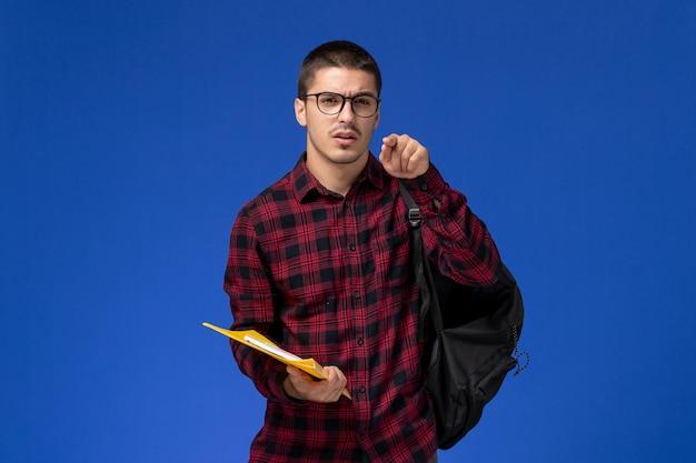 Vista frontal del estudiante en camisa a cuadros roja con mochila con archivos y cuaderno en la pared azul claro