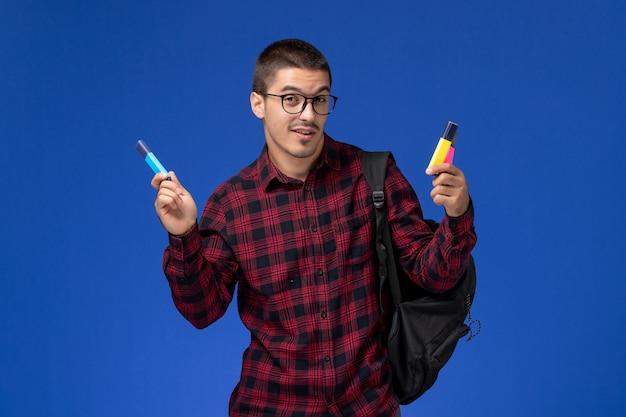 Vista frontal del estudiante en camisa a cuadros roja con mochila sosteniendo rotuladores en la pared azul claro