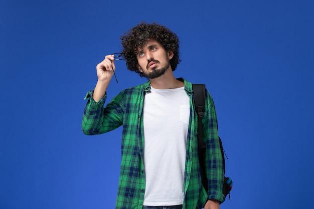 Vista frontal del estudiante en camisa a cuadros verde con mochila negra pensando en la pared azul