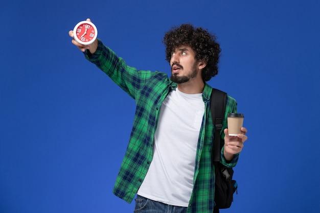 Vista frontal del estudiante en camisa a cuadros verde con mochila negra y sosteniendo el reloj y el café en la pared azul