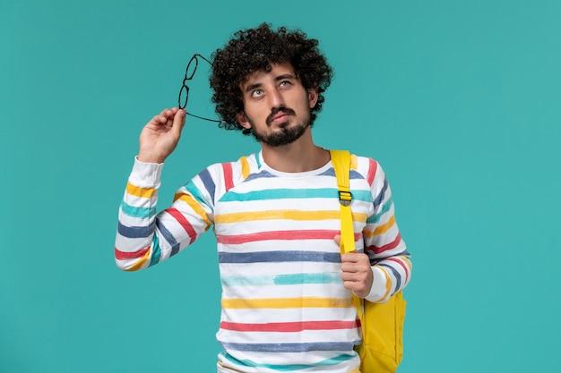 Vista frontal del estudiante en camisa a rayas con mochila amarilla sosteniendo sus gafas de sol ópticas pensando en la pared azul