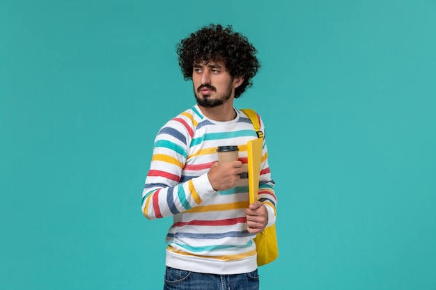 Vista frontal del estudiante en camisa a rayas vistiendo una mochila amarilla sosteniendo archivos y café en la pared azul
