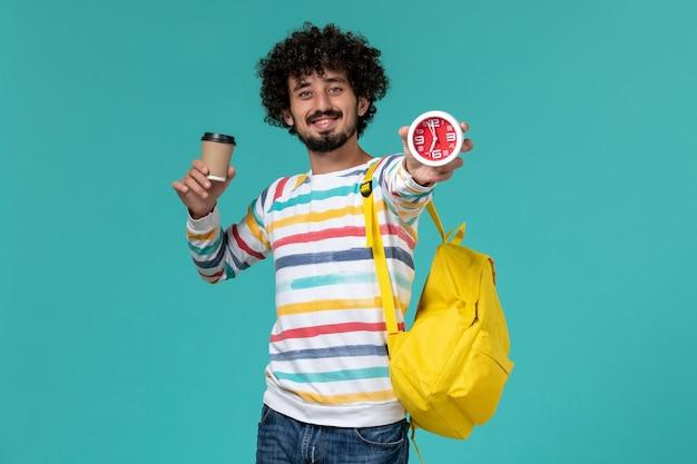 Vista frontal del estudiante en camisa a rayas vistiendo una mochila amarilla sosteniendo café y relojes sonriendo en la pared azul