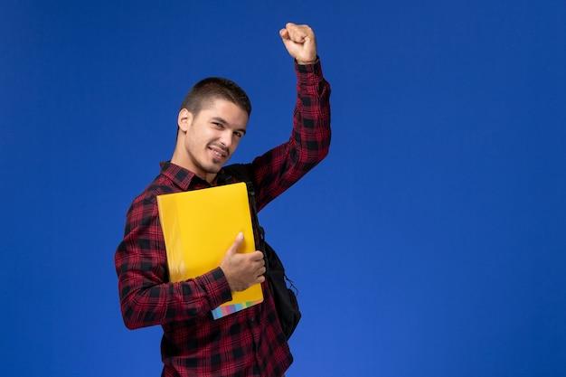 Vista frontal del estudiante en camisa roja a cuadros con mochila sosteniendo archivos amarillos en la pared azul