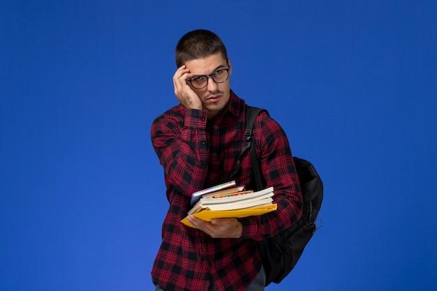 Vista frontal del estudiante en camisa roja a cuadros con mochila sosteniendo cuadernos en la pared azul claro