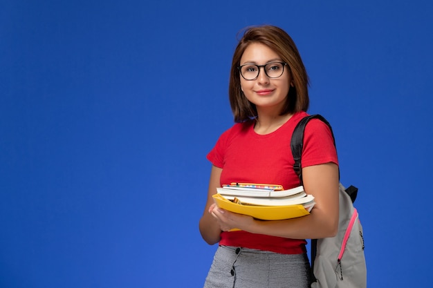 Vista frontal de la estudiante en camisa roja con mochila sosteniendo libros y archivos sonriendo en la pared azul